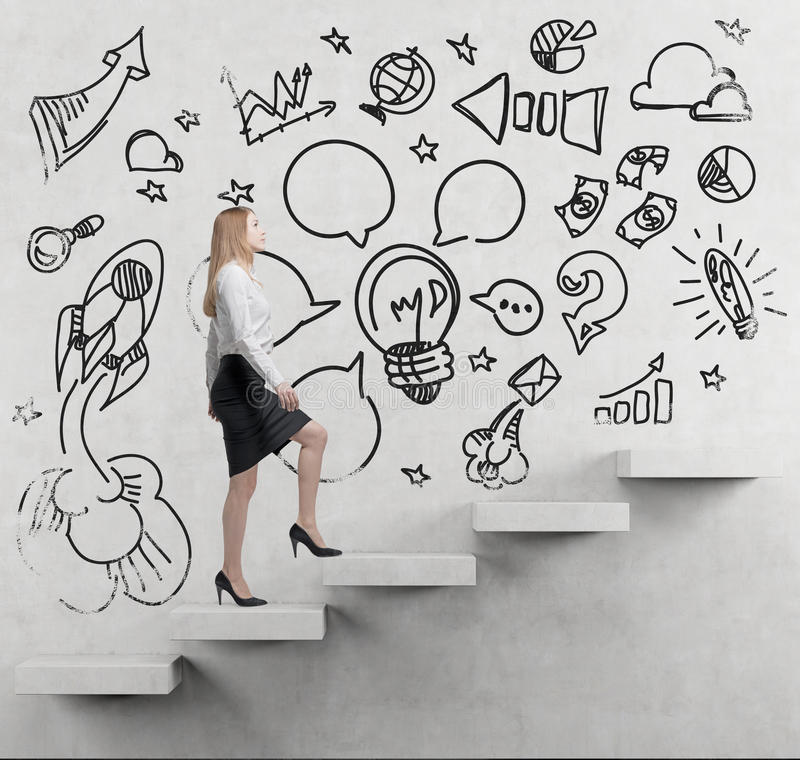 Young business woman is going up to the stairs. A concept of a brainstorm. Business icons are drawn on the wall. royalty free stock photos