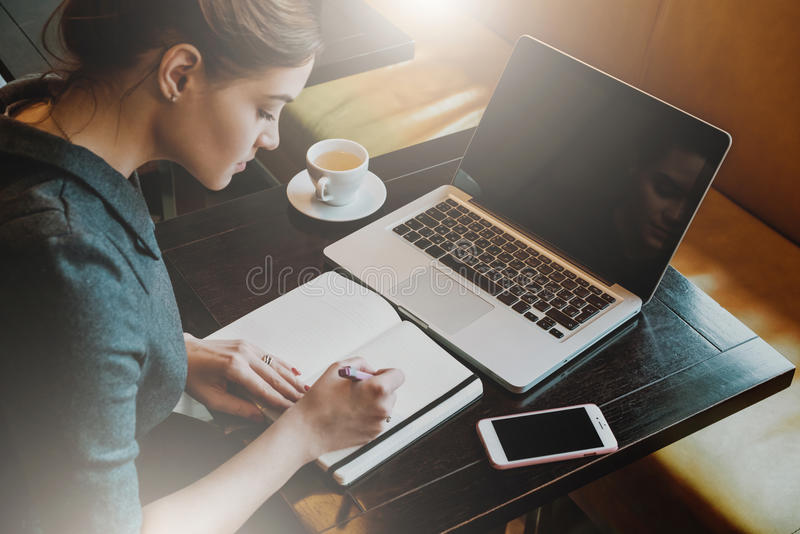 Young business woman in gray dress sitting at table in cafe and writing in notebook. royalty free stock photos