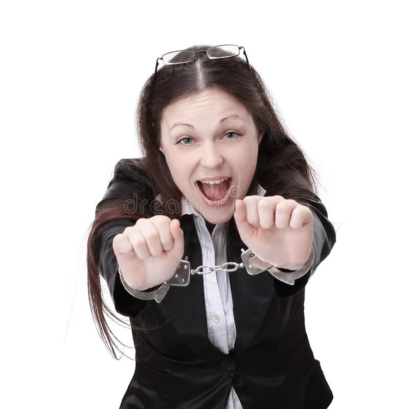 Young business woman in handcuffs,sitting behind a Desk. stock image