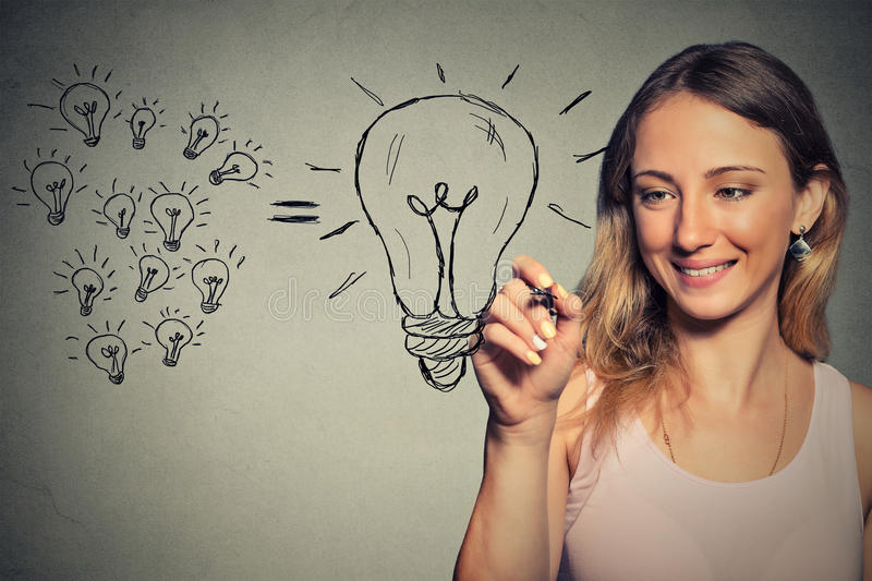 Young business woman has a big idea. Drawing light bulb royalty free stock photography