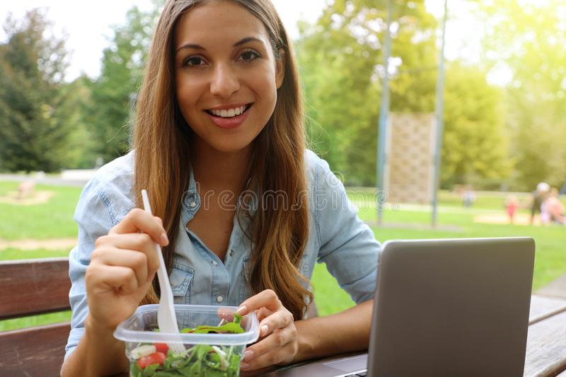 Young business woman have a lunch sitting in city park looking at camera stock photos