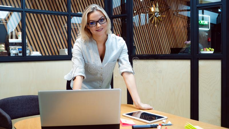 Young business woman in her office. Work in the office, a professional girl stands near the table with a laptop. stock images