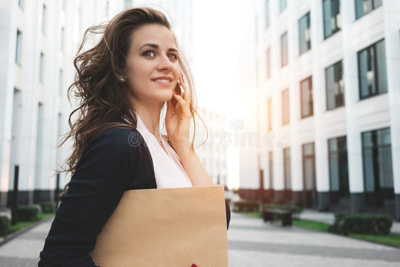 Young business woman hold in hand document folder and securities among urban space and talking on the phone. Flare effect royalty free stock images