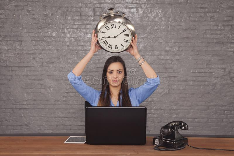 Young business woman holding a clock over her head, concept of b royalty free stock photo