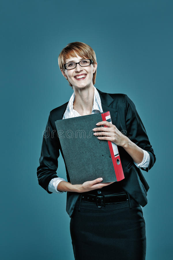 Young business woman holding a folder with documents and smiling to the camera stock photos