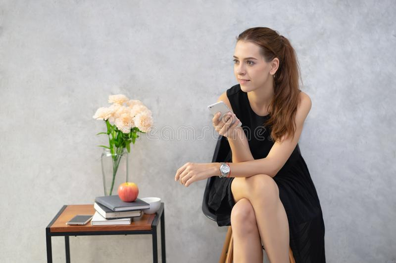 Young business woman holding mobile phone and looking away at modern office. stock photography