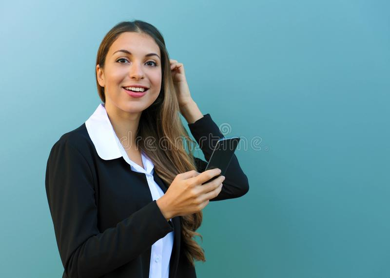 Young business woman holding mobile phone looking at camera against blue background outdoors. Copy space royalty free stock photos