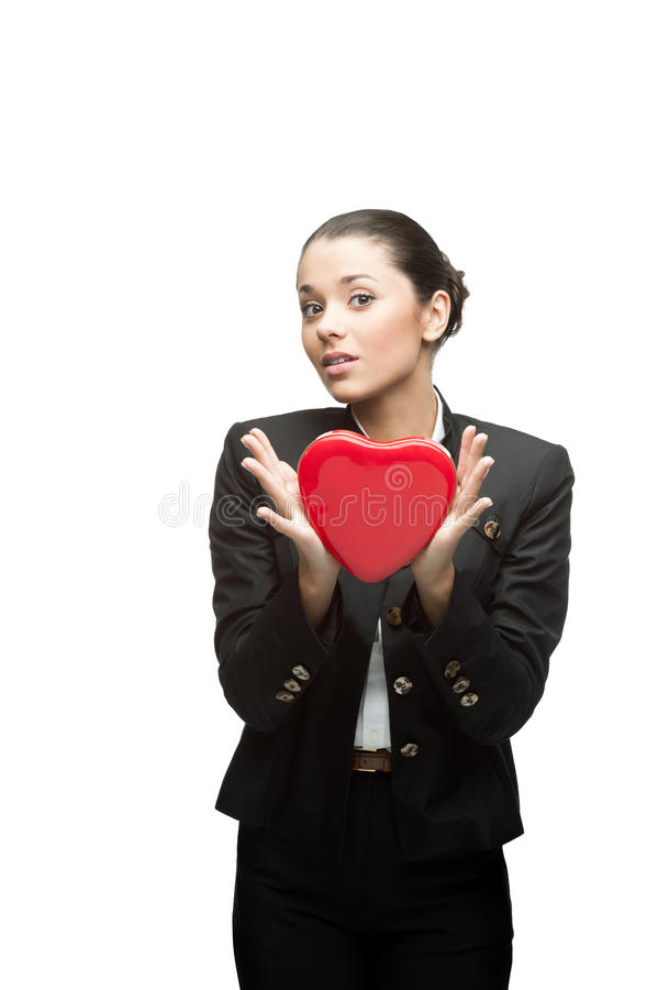 Young business woman holding red heart. Young caucasian business woman in black suit holding red heart isoalted on white royalty free stock photography