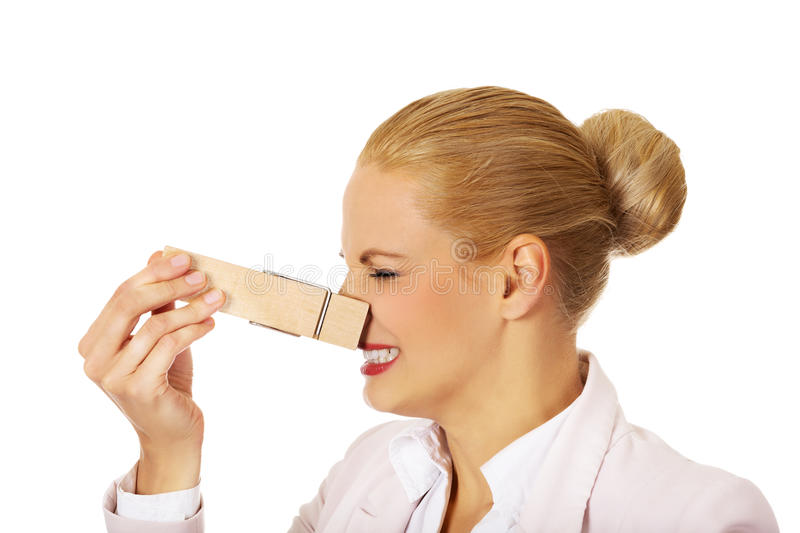 Young business woman with huge clothespin on her nose. Stinks concept.  royalty free stock photos