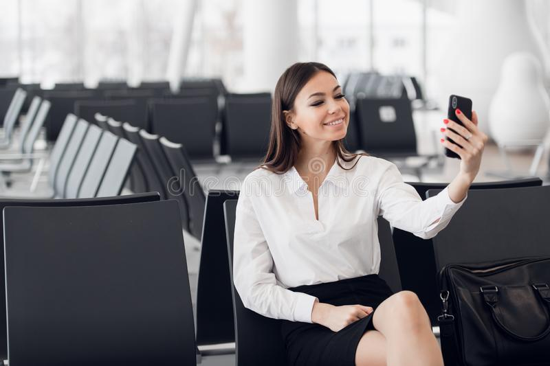 Young business woman at international airport, making selfie with mobile phone and waiting for her flight. Female royalty free stock images