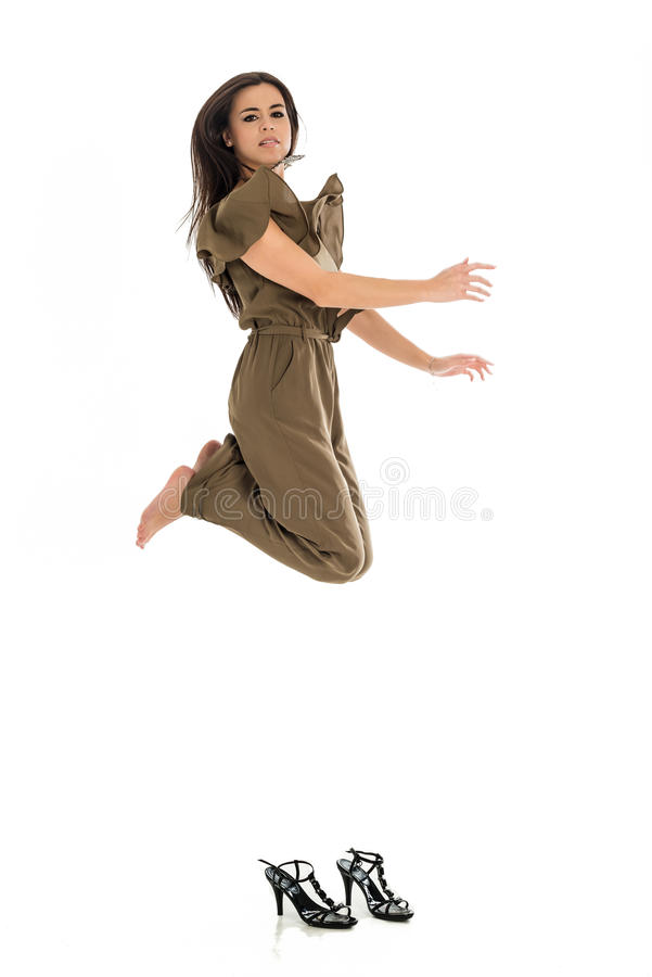 Young business woman jumping high. With shoes on the ground over white background stock image