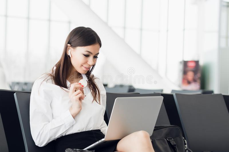 Young business woman with laptop and healthy snack in her hand sitting at departures terminal gate. Traveler waits for. His transport connection. Waiting at the stock photos