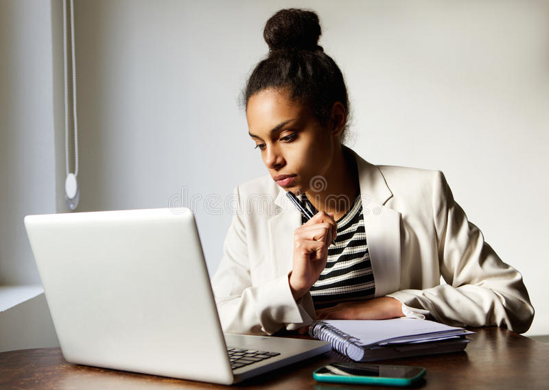 Young business woman with laptop thinking. Close up portrait of young business woman with laptop thinking royalty free stock photography