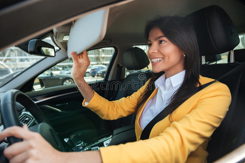 Young business woman looking in mirror while driving car royalty free stock images
