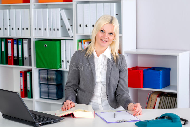 Young business woman in office. Young blond business woman in the office royalty free stock photography
