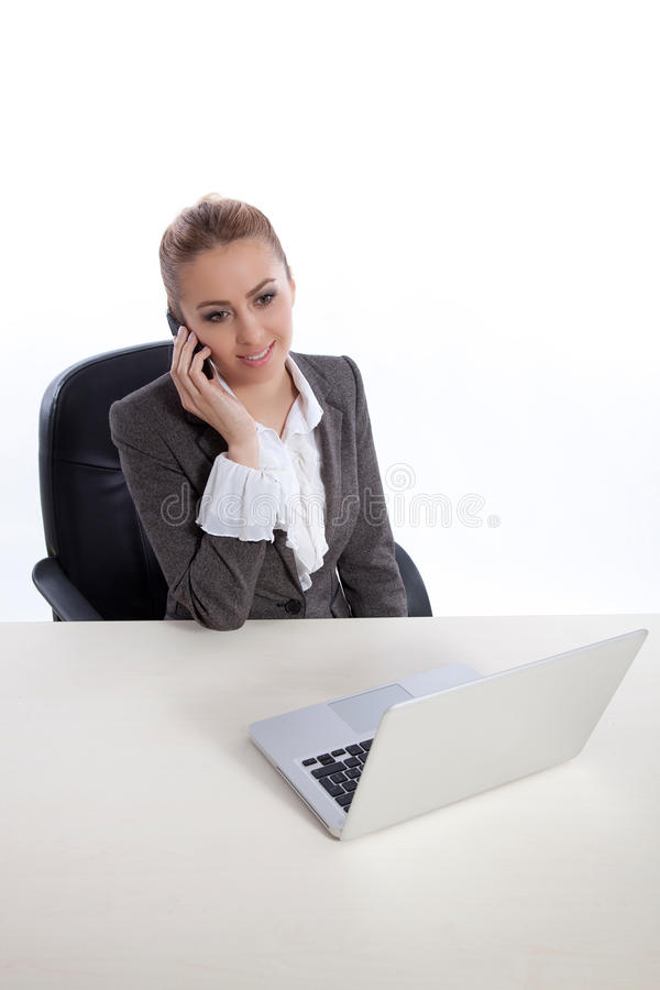 Young business woman at office calling by telephon. E, working on laptop, white background royalty free stock photo