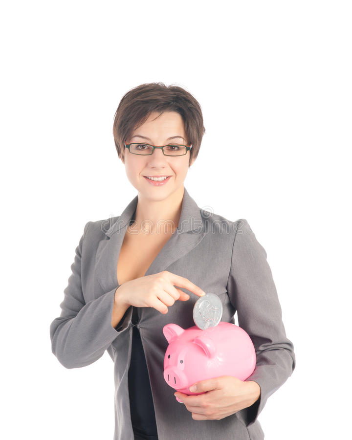 Young business woman with piggy bank. Young woman in business suit dropping quarter dollar coin into pink piggy bank royalty free stock photos