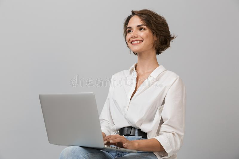 Young business woman posing isolated over grey wall background sitting on stool using laptop computer royalty free stock photos