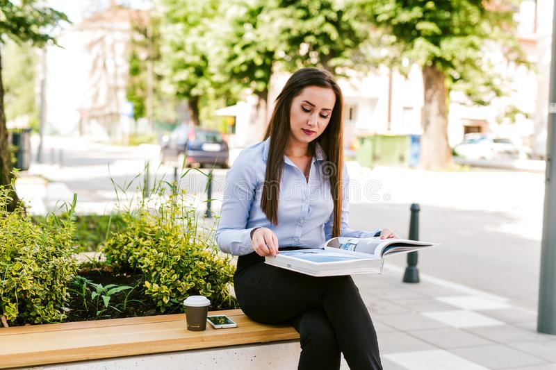 Young Business Woman Reading Book While Drinks Coffee Outdoor stock photos