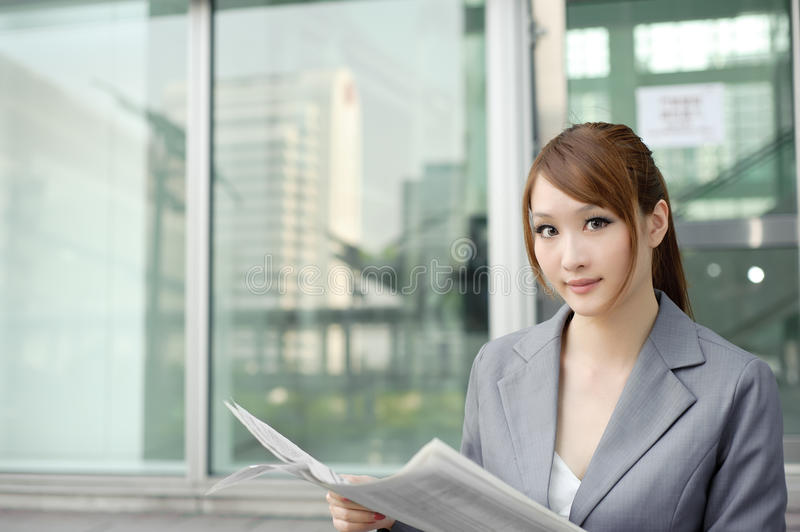 Young business woman reading newspaper royalty free stock photography