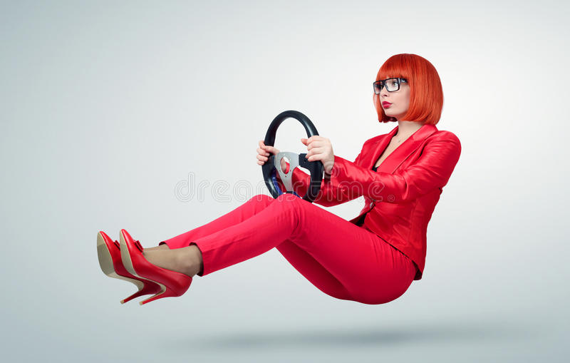 Young business woman in red driver car with a wheel stock image