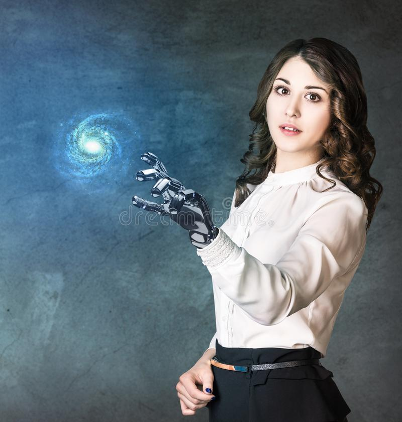 Young business woman with robot hand point on galaxy. Elements of this image furnished by NASA royalty free stock photography