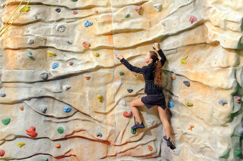 Young business woman on rock wall. Active young business woman on rock wall in sport center stock photos