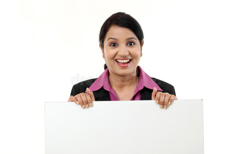 Young business woman showing blank signboard. Cheerful business woman showing blank signboard against white stock images