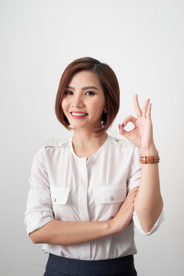 Young business woman showing OK sign on white background royalty free stock photo