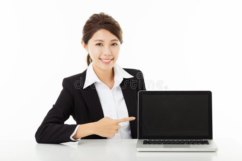 Young business woman showing and pointing to the laptop. Smiling young business woman showing and pointing to the laptop stock images