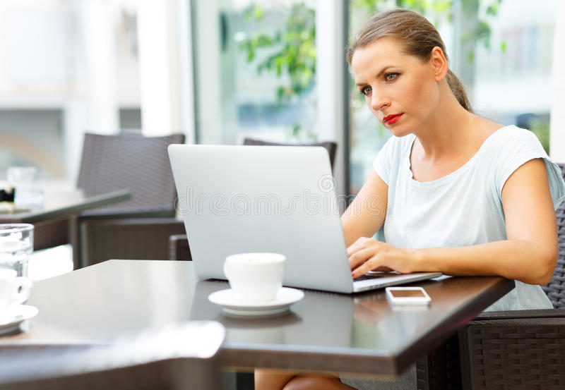Young business woman sitting in a cafe with a laptop and coffee stock images