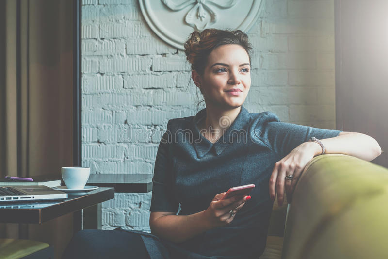 Young business woman sitting in cafe at table, leaning his hand back in chair,looking out window and holding smartphone. Young smiling business woman sitting in stock photography