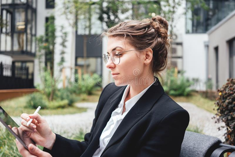 Young business woman sitting at coffee shop working on digital tablet. Businesswoman at cafe on veranda using gadgets for digital work. Young business woman royalty free stock photos