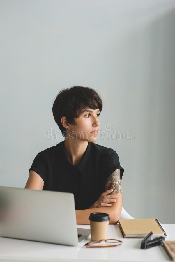 Young business woman sitting at the desk with arms crossed and looking away. stock photos