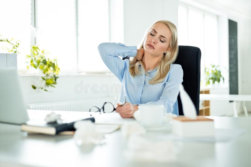 Young businesswoman suffering flu at work stock photos