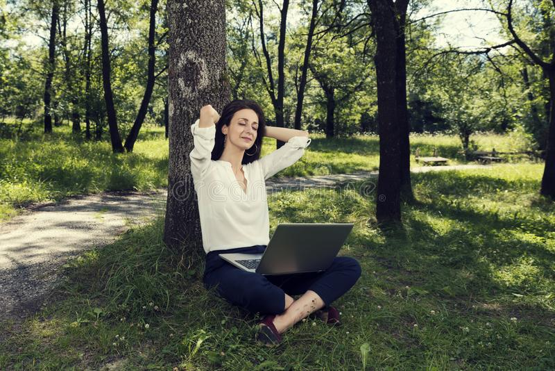 Young business woman sitting on a ground with her laptop and enjoying her  break in a public park. Selective focus stock photography
