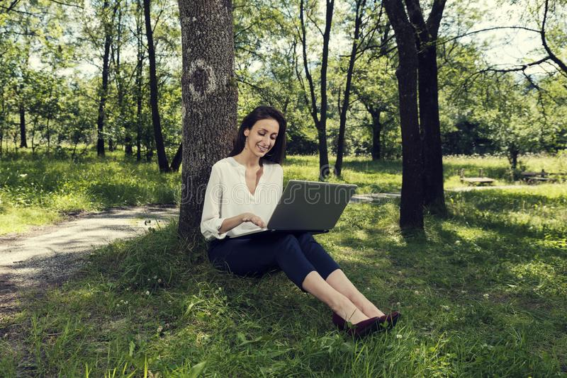 Young business woman sitting on a ground and working on her laptop in a public park and smiling royalty free stock photos