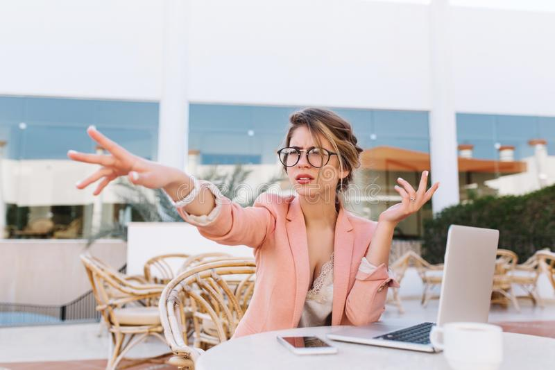 Young business woman sitting in outdoor cafe with laptop on table, serious lady pointing with hand direction, saw royalty free stock images