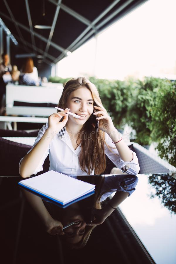 Young business woman sitting at table in cafe, talking oncell phone while taking notes in notebook on table laptop. Student learni royalty free stock images