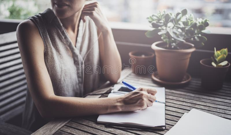 Young business woman sitting at table in caffee terrace and taking notes in notebook.On table is smartphone and paper royalty free stock images
