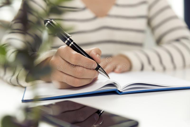 Young business woman sitting at table and writing in notebook. O. N table is smartphone, and tablet. Freelancer working, writing down new ideas stock photo