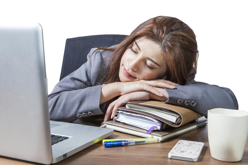 Young business woman sleeping at workplace. Business woman sleeping on laptop taking a power nap during work Isolated stock image