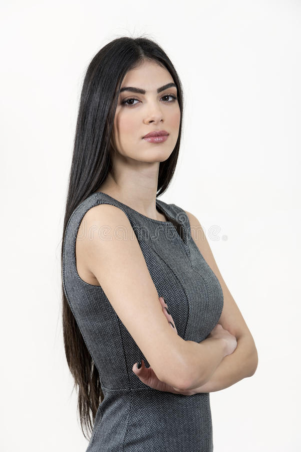 Young business woman standing with arms crossed. Young business woman standing with her arms crossed and looking at the camera. She has black long hair and royalty free stock image