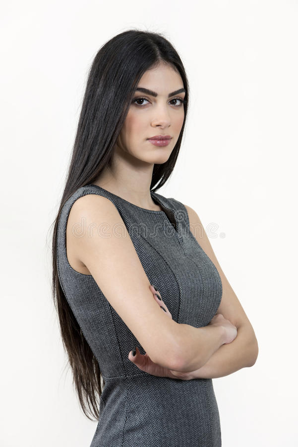 Young business woman standing with arms crossed. Young business woman standing with her arms crossed and looking at the camera. She has black long hair and stock image