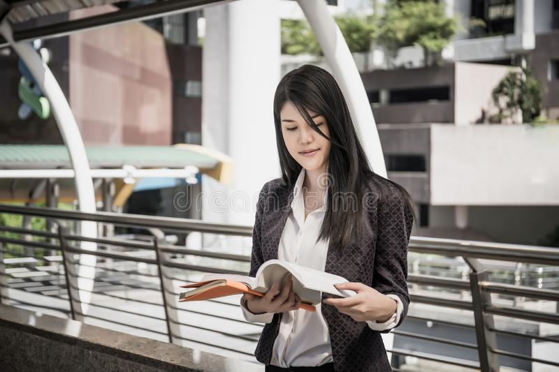 Young business woman standing reading the business report during a walking royalty free stock image