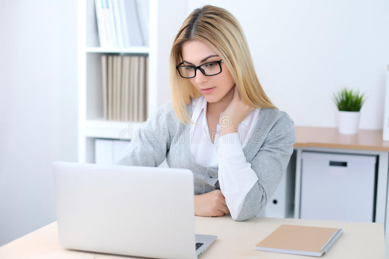 Young business woman or student girl sitting at office workplace with laptop computer. Home business concept.  stock photography