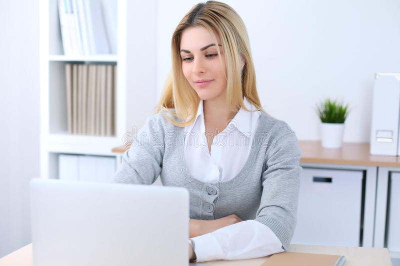 Young business woman or student girl sitting at office workplace with laptop computer. Home business concept.  royalty free stock images