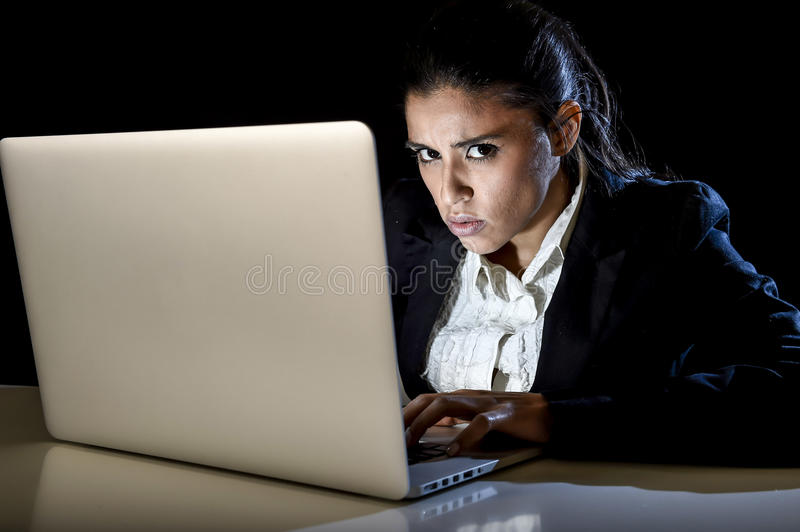 Young business woman or student girl working in darkness on laptop computer late at night concentrated. Young business woman or student girl working in darkness stock photography
