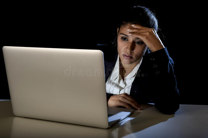 Young business woman or student girl working in darkness on laptop computer late at night looking concentrated. Young latina business woman or student girl stock photos