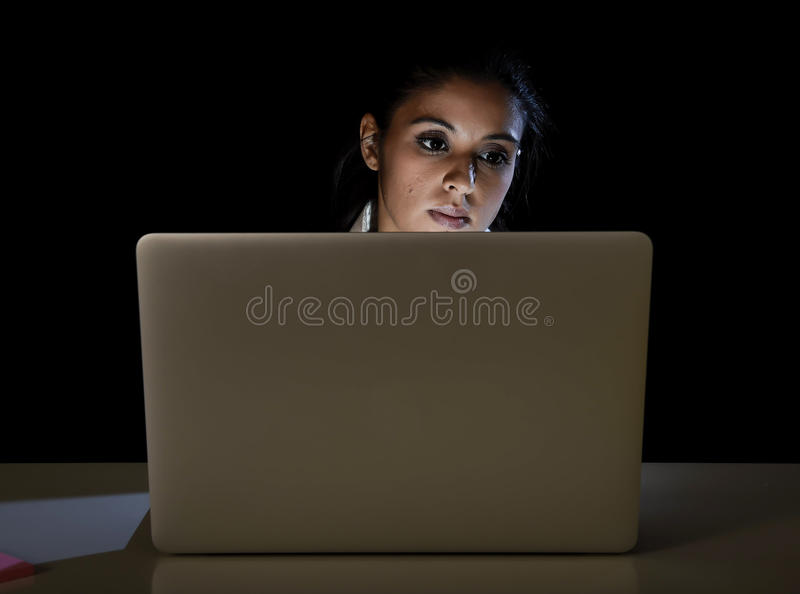 Young business woman or student girl working in darkness on laptop computer late at night looking concentrated. And tired in long hour of work concept isolated stock photo